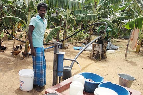 チューブ井戸で水を汲む住民