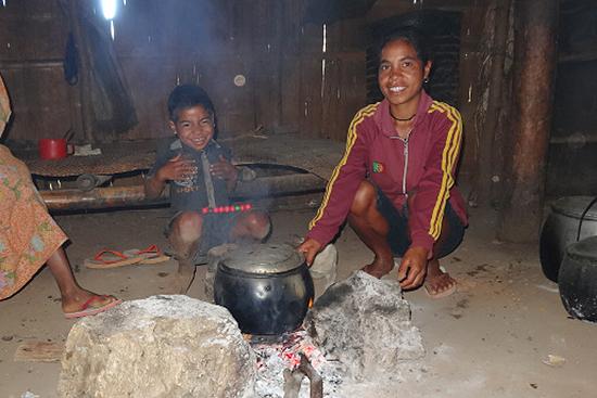 調理風景。真ん中の子供が、かまどから出る煙で少し白く見えます。
