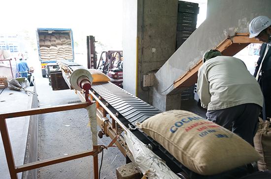 1袋ずつベルトコンベアーに乗せて、倉庫の奥へと運ぶ