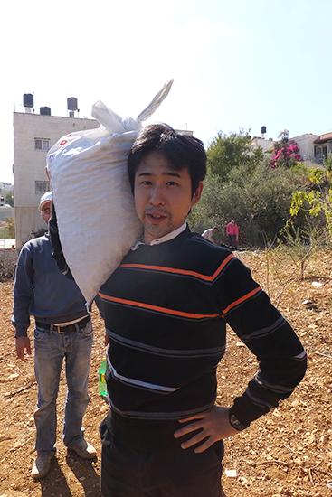 収穫したオリーブが入った袋を担いでみました