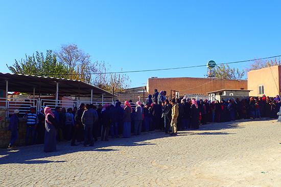 配給を待つ人々の長い列。ほとんどが男性ですが、女性と子どもだけで訪れる家族も。