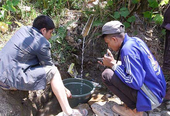 水源の水量を調査するスタッフ