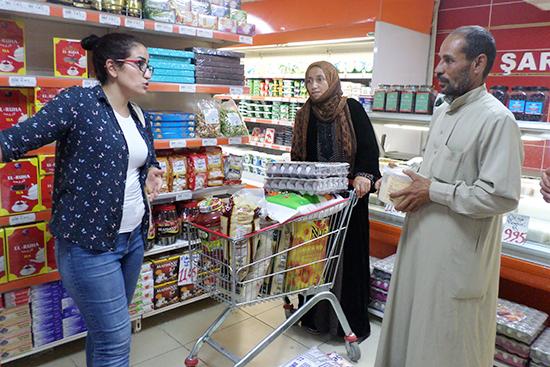 スーパーにて買い物中の支援対象者に対し、商品の購入ルールをスタッフ(写真左)が再確認