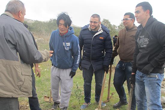 植樹をするボランティアさんからの質問に答える農業専門家