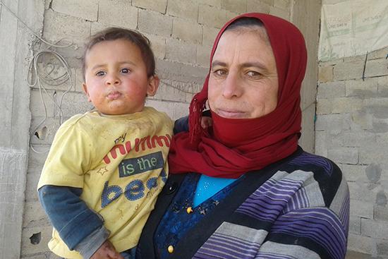 お母さんに抱っこされたムハンマドくん。当団体の支援が、彼の粉ミルク購入代に。