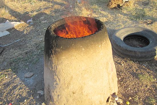 手製の簡易窯。パン生地を窯の中の壁に貼り付けパンを焼く。ラマダン終了後の食事の準備中。