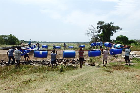 漁民みんなで生簀を池に運んでいます