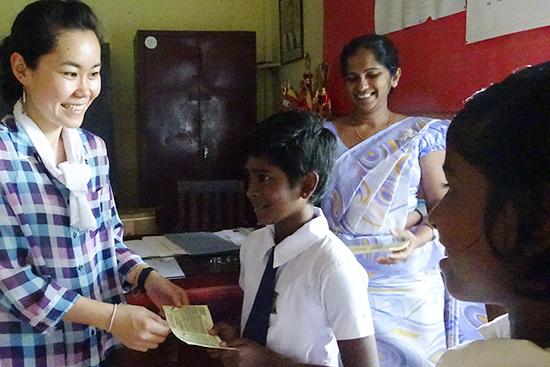 メデルピティヤの学校での子どもへの靴の配布の様子;バウチャーを配布して、後ほど近くの靴店で必要なサイズの靴と交換してもらう)