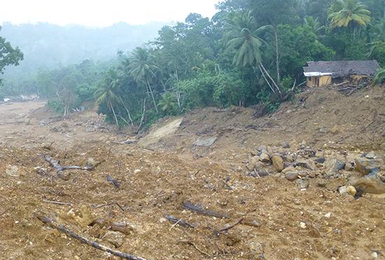 ヌワンさんの家(写真右)が土石流の経路ぎりぎりの所に残っています。7月下旬現在、ヌワンさん一家を含めて16世帯が公共の施設で避難生活を続けています。
