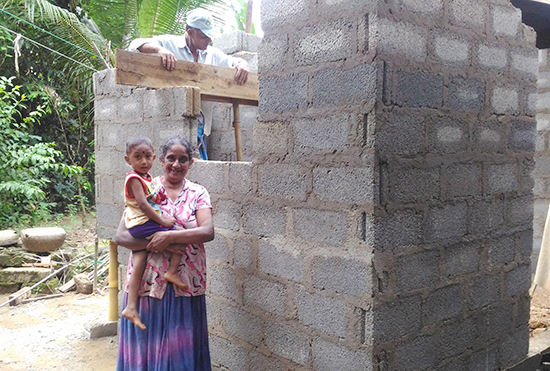 洪水で土壁のキッチンが流されてしまった南パッレガマ村のダヤナンダさんの奥さんとお孫さん。基礎の部分、壁はほとんど完成です。コンクリートブロックで作るキッチンは、また洪水が起こっても流されることがないと安心しています。