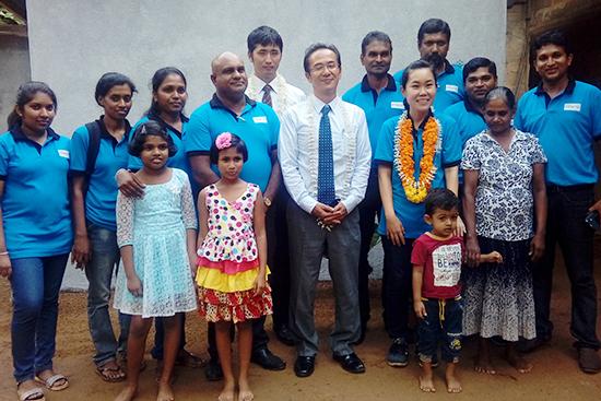 マリカさん(右から2番目の女性)の完成した台所の前で集合写真:青いシャツはみんなパルシックスタッフです。中央は在スリランカ日本大使館から駆けつけてくださった公使と職員の方です。