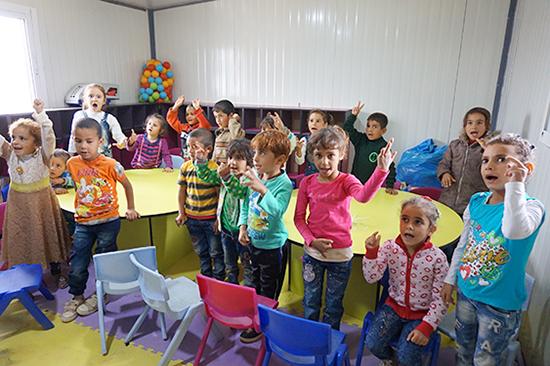 就学前教育の児童の教室の様子。先生の動きを真似て手遊びしています