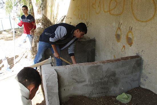 学校の庭に設置した簡易堆肥舎での床材づくり