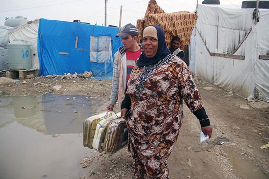 家じゅうが水浸しとなってしまった世帯に毛布と灯油を届けるスタッフと、配布を受け取り、安堵の表情を見せるお母さん。