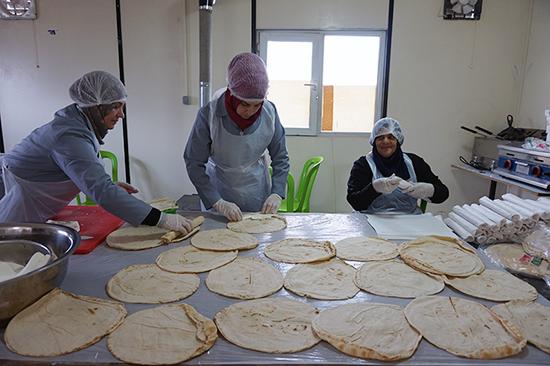 パルシックが支援するパン工場で製造したパンで、シリア人のお母さんたちがサンドイッチを作っています。