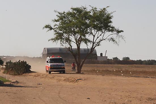緩衝地帯の農地横を通り過ぎる救急車(写真提供:PARC Gaza)