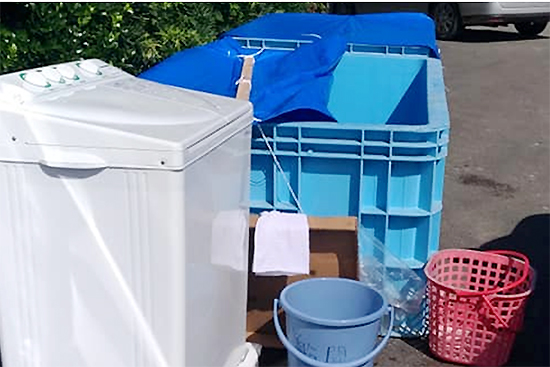 共同で使える洗濯機。生活用水にも、誰かがブルーシートでふたを付けていました。