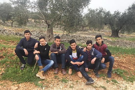 オリーブの木の前で歯に噛みスマイルの男子学生たち