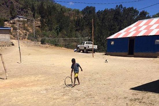 車輪を転がして遊ぶ集落の子ども