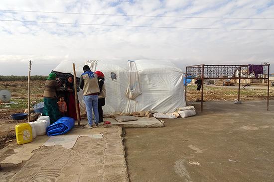 穴が開いたテントで暮らすシリア人世帯