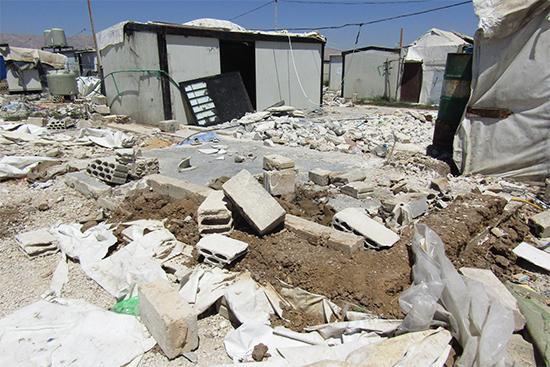 難民が自主的に破壊したシェルターの跡。奥にあるのはまだ取り壊されていないシェルター。