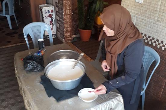 生産したミルクからチーズを作る女性