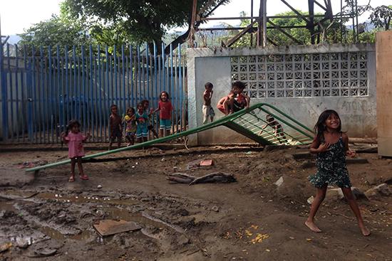 倒れた門扉をジャングルジム代わりに遊ぶ子どもたち