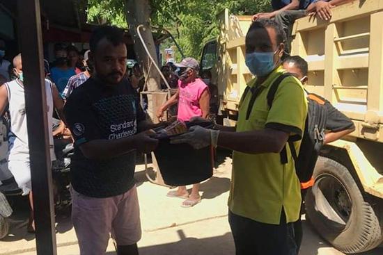 タフ・ララン集落の被災者へ物資の手渡し